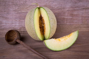Juicy honeydew melon on a wooden table background.