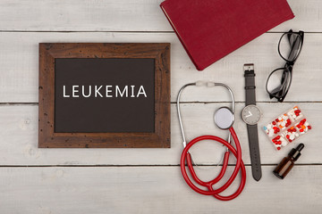 "blackboard with text ""Leukemia"", pills, book, eyeglasses, watch and stethoscope"