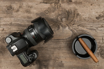 Digital camera and ashtray with a cigar on an old wood.