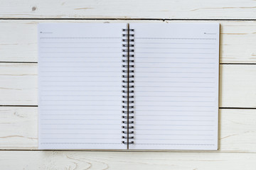 Open notebook with blank pages on wood table