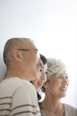 Family standing side by side, smiling, white background