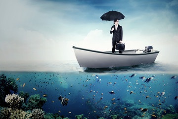 Businessman with umbrella and bag on boat