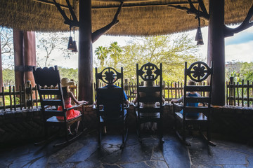Rear view of young family sitting together on the thatched roof balcony of their tropical island hotel. People sitting in rocking chairs are silhouetted against the scenic island setting.