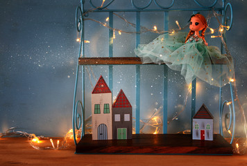 Cute doll and wooden little houses next to warm garland lights