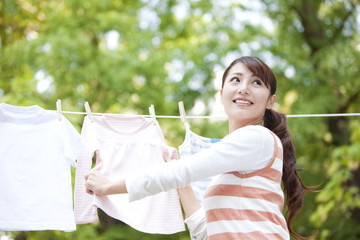 Woman drying laundry, smiling and looking back