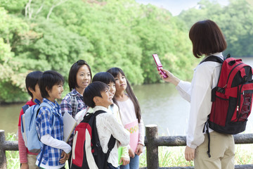 School children and female teacher in park, teacher taking picture of students by mobile phone