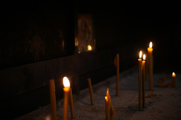 Burning candles in the Orthodox Church on the background of the icon of Our Lady.