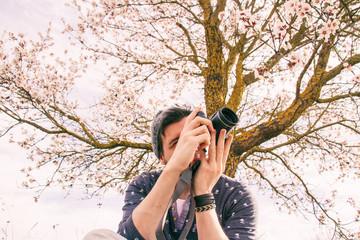 Joven fotógrafo disfrutando de su pasión apoyado en un árbol en flor en primavera