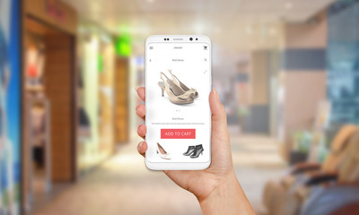 Online shop on mobile phone display. Modern white smart phone with round edges in girl hand. Shopping mall in background.