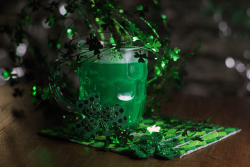 St patricks day. St. Patricks Day decoations with green beer. Irish green beer, traditional alcohol for St. Patrick's day holiday celebration. Glass of green beer with clover leaves on wooden table.