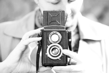 Old camera in the hands of a young girl