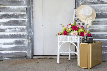basket of flowers on wicker chair with hat by wooden door