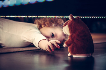 Playful cute curious baby pulling hand to toy under the bed in vintage style