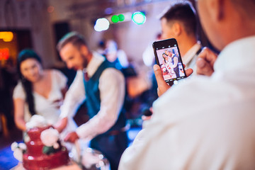 Man with phone make a photo bride and groom