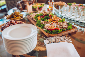 Buffet table of reception with cold snacks, meat and ham