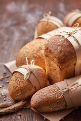 different bread on the wooden table, flour, paper bags, rope. Brown background.