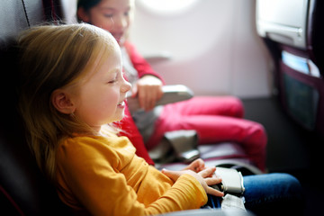Two adorable little girls traveling by an airplane. Children sitting by aircraft window and looking outside.
