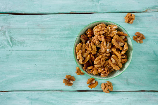 walnuts in a bowl on turquoise surface