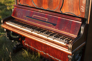 Old brown classical piano in the middle of the field outside and staying on the green grass
