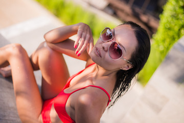 Close up summer portrait of Woman enjoy relaxing in the pool.Beautiful brunette hair sexy woman young girl model in sunglasses and elegant red sexy swimsuit lingerie with around the pool
