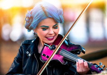 Woman perform music on violin in park outdoor. Girl with blue hairstyle performing jazz on city street . Spring outside blur background.