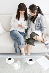 Two women sitting on sofa text messaging