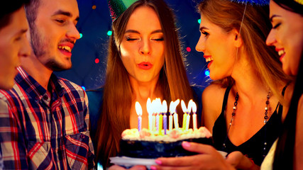 Happy friends birthday celebrating food with celebration cakes. Meet people wear in hat party blow out candles at burning candles. Women and men have fun in nightclub.Youth shout surprise together.