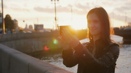 Young beautiful girl taking selfie on the background of the bridge in the bright rays of the setting sun. 4K