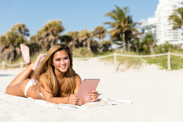 Smiling happy asian woman lying on beach using tablet computer