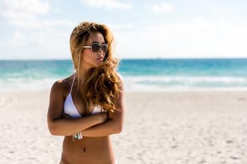 Woman in bikini on ocean beach posing with arms crossed looking away from camera