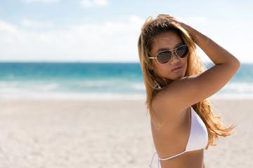 Sexy ethnic woman in white bikini and sunglasses on beach vacation