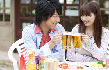 Young couple toasting with beer