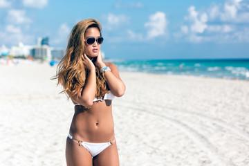Portrait of pretty beautiful woman in white bikini posing in sunshine on vacation