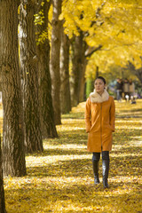 Mid adult woman standing by Ginkgo trees