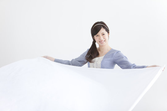Young Woman Spreading Sheet
