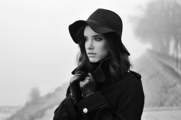 Beautiful sad girl in black clothes, black hat and leather gloves outdoor on moody winter day