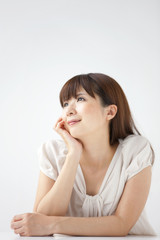 Young woman on white background, resting chin on hand