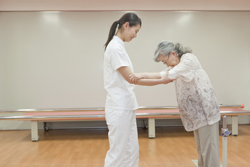 Nurse helping a senior woman walk, Kanagawa Prefecture, Honshu, Japan