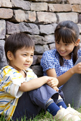 Girl and boy sitting by brick wall
