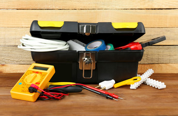 Box with electrician tools on wooden background