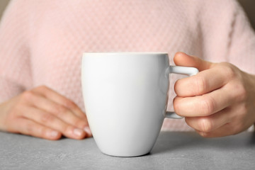 Woman holding blank cup, closeup