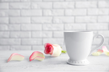 Cup and flower on white brick wall background