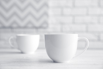 Blank ceramic cups on white table