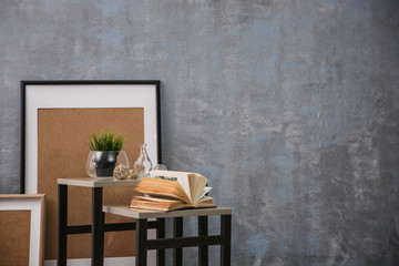 Tables with home decor on grey wall background