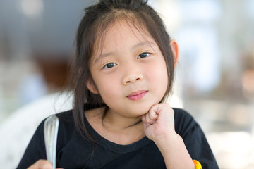 Portrait of Cute Asian Child at Restaurant Holding Spoon