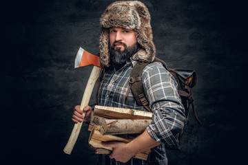 Portrait of brutal bearded hunter male holds an axe on his shoulder.