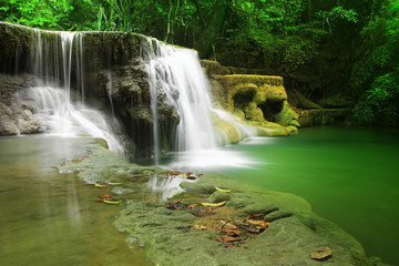 waterfall with clear green emerald water and rock for relax with tree and root in the jungle at Huay Mae Khamin waterfall for nature landscape and background