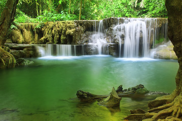 waterfall with clear green emerald water and rock for relax with tree and root in the jungle or forest at Huay Mae Khamin waterfall for nature landscape and background
