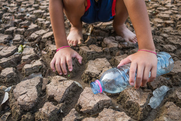 Children pour water on the arid ground, Drought concept.