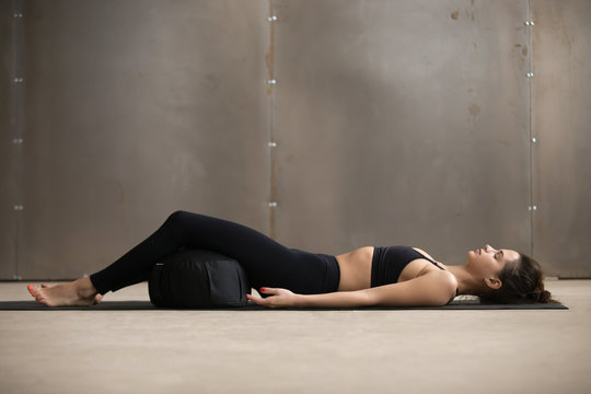 Young attractive sporty yogi woman practicing yoga, lying in Savasana exercise, Dead Body, Corpse pose using Zafu cushion for comfort, resting after working out, urban style grey studio, full length